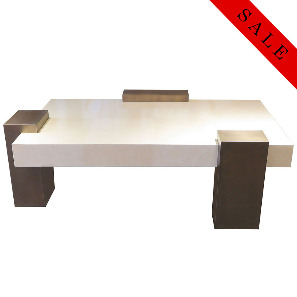 chunky 3-legged coffee table with cream top and brass painted legs